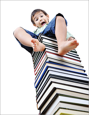 boy sitting atop a pile of books
