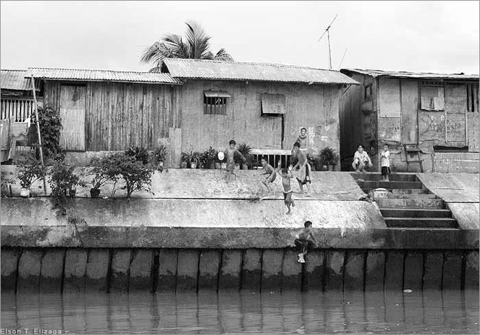 Houses, dike, and children at Cagayan River