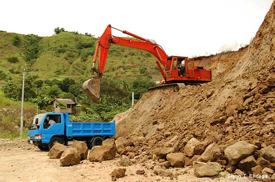 Quarrying in the Huluga archaeological site showing blue pickup truck and red backhoe.
